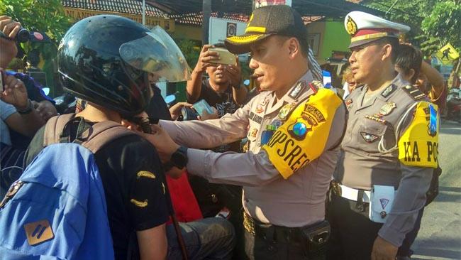 AKBP Awan Hariono saat memberikan contoh cara memakai helm yang benar kepada pengendara roda dua (im)