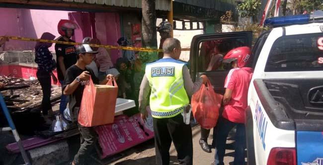 Anggota kepolisian membantu mengevakuasi barang dagangan yang masih bisa diselamatkan