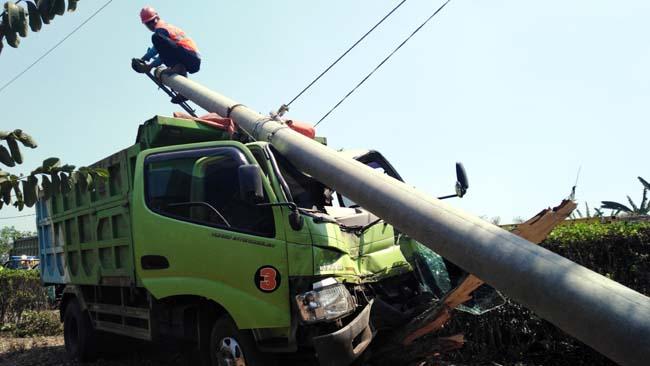 Petugas PLN saat memperbaiki kabel dan tiang listrik yang menyangkut body truk (gus HP)