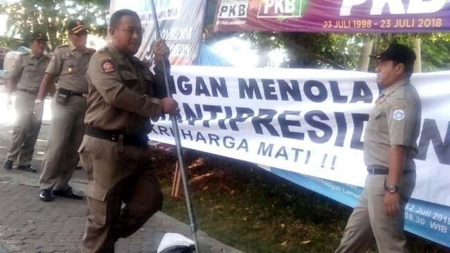 Satpol PP menurunkan sejumlah spanduk penolakan #2019 Ganti Presiden yang terpasang di sejumlah titik di wilayah Lamongan