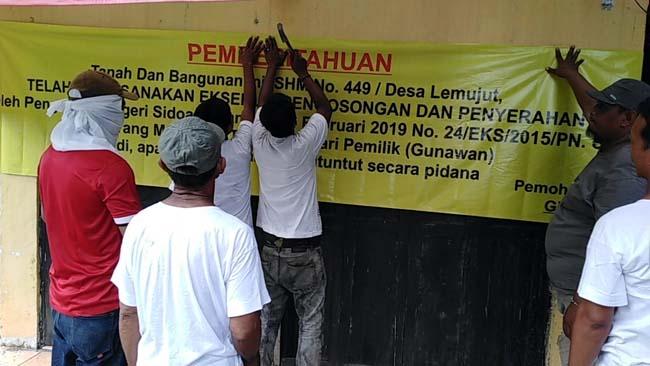Tim juru sita Pengadilan Negeri Sidoarjo, memasang beaner pemberitahuan (gus)