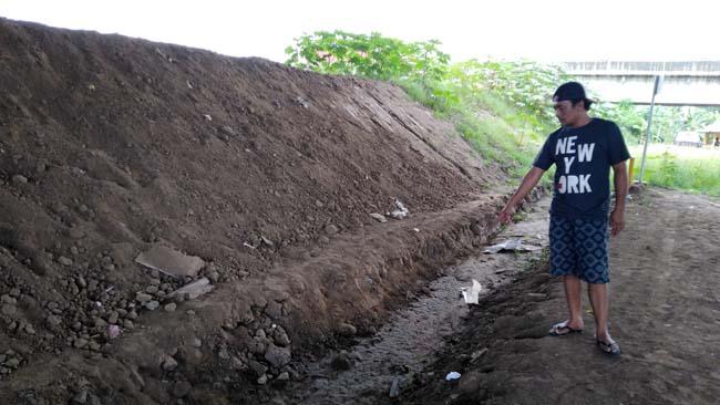 Edi Suparno menunjukan jalan kondisi rusak dan pecah di kawasan Dusun Kluweh, Desa Kebonagung, Porong (gus)