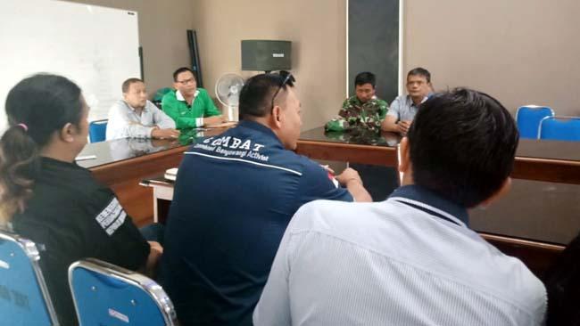 MASIH DIDUGA : Kades Genteng Kulon Supandi (Kaos Hijau) didampingi Pendamping Desa Iqbal, saat menjelaskan biaya PTSL kepada LSM Cambat dan membantah adanya pungli. (tut)