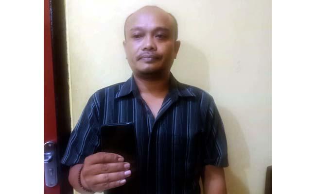 NGAKU JURNALIS TAPI PANJANG TANGAN : Samsul Hadi Leo alias Jambrong menunjukkan barang bukti (BB) berupa HP saat diperiksa penyidik Polsek Kota Banyuwangi. (ras)