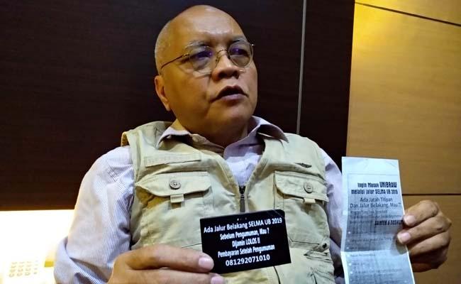 Ketua Tim Advokasi Hukum UB Dr Prija Djatmika SH MSi, menunjukkan brosur dalam amplop. (rhd)