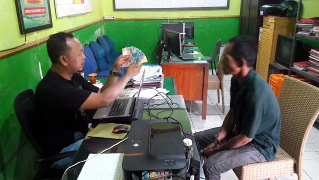 Kanit Reskrim Polsek Tanah Merah, Aipda Priyanto(kiri) saat menunjukan barang bukti hasil uang palsu di depan tersangka pengedar upal, Abdul Fatah (Kanan)