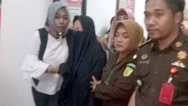 Lilik Wijayanti Budi Utami menggunakan penutup wajah saat digelandang petugas Kejari Kab.Pasuruan menuju LP Bangil